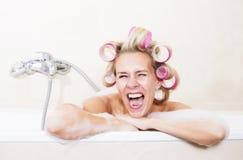 Mujer con los bigudíes en bañera fotos de archivo libres de regalías