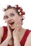 Mujer con los bigudíes en su pelo que parece sorprendido. Imagen de archivo libre de regalías
