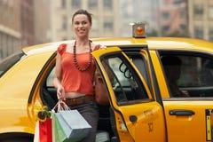 Mujer con los bolsos de compras que salen el taxi Imágenes de archivo libres de regalías