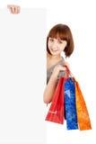 Mujer con los bolsos de compras que sostienen la cartelera en blanco Imagen de archivo
