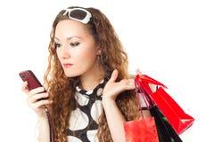 Mujer con los bolsos de compras y el teléfono móvil Imagen de archivo