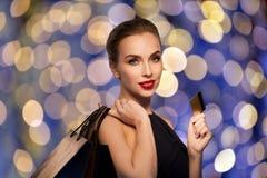 Mujer con los bolsos de la tarjeta de crédito y de compras Fotografía de archivo libre de regalías