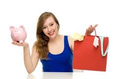 Mujer con los bolsos del piggybank y de compras Imágenes de archivo libres de regalías