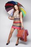 Mujer con los bolsos y el paraguas de compras Fotos de archivo