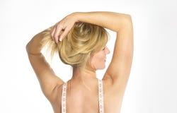 Mujer con los brazos aumentados sosteniéndose el pelo en su cabeza Hombros desnudos con una cinta métrica alrededor de su cuello foto de archivo libre de regalías