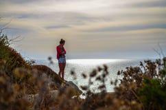 Mujer con los brazos cruzados haciendo una pausa la orilla Foto de archivo