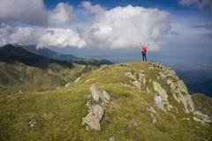 Mujer con los brazos estirados en las montañas Imagenes de archivo