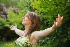 Mujer con los brazos extendidos en campo Imagen de archivo libre de regalías