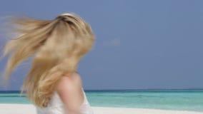 Mujer con los brazos extendidos en la playa hermosa almacen de video