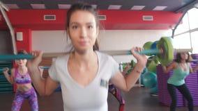 Mujer con los brazos musculares que levanta el barbell grande en clase de entrenamiento de la aptitud con otros adultos metrajes