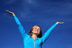 Mujer con los brazos outstretched contra el cielo azul Foto de archivo libre de regalías