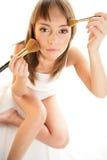 Mujer con los cepillos del maquillaje Foto de archivo