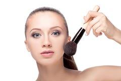 Mujer con los cepillos del maquillaje imagenes de archivo
