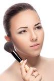 Mujer con los cepillos del maquillaje fotografía de archivo