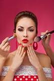 Mujer con los cepillos del maquillaje Ella se está colocando foto de archivo