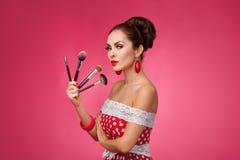 Mujer con los cepillos del maquillaje Ella se está colocando imagen de archivo