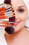 Mujer con los cepillos para el maquillaje foto de archivo