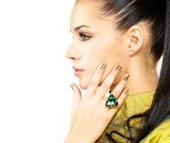Mujer con los clavos de oro y la esmeralda de la piedra preciosa Fotos de archivo