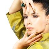 Mujer con los clavos de oro y la esmeralda de la piedra preciosa Fotografía de archivo libre de regalías