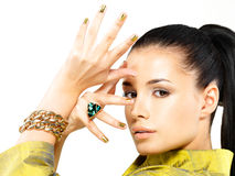 Mujer con los clavos de oro y la esmeralda de la piedra preciosa Foto de archivo libre de regalías