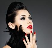 Mujer con los clavos rojos y el peinado creativo Fotos de archivo