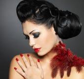 Mujer con los clavos rojos y el peinado creativo Imagen de archivo libre de regalías