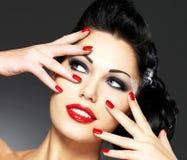 Mujer con los clavos rojos y el peinado creativo Imagen de archivo