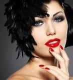 Mujer con los clavos rojos y el peinado creativo Foto de archivo libre de regalías