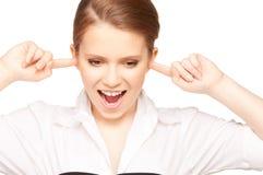 Mujer con los dedos en oídos Imagenes de archivo