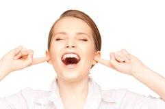 Mujer con los dedos en oídos Fotos de archivo