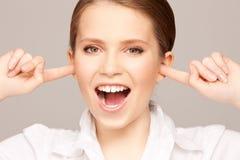 Mujer con los dedos en oídos Foto de archivo libre de regalías