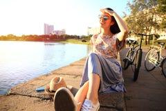 Mujer con los dientes blancos que piensa y que mira de lado en un parque en verano Foto de archivo libre de regalías