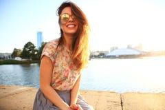 Mujer con los dientes blancos que piensa y que mira de lado en un parque en verano Imagen de archivo libre de regalías