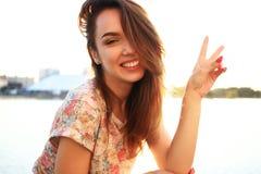 Mujer con los dientes blancos que piensa y que mira de lado en un parque en verano Imágenes de archivo libres de regalías