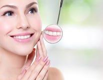 Mujer con los dientes de la salud y el espejo de boca del dentista Imagen de archivo libre de regalías