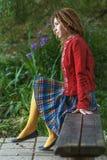 Mujer con los dreadlocks que se sientan en banco Foto de archivo libre de regalías