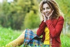 Mujer con los dreadlocks que se sientan en hierba Imágenes de archivo libres de regalías