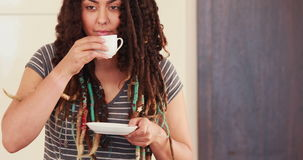 Mujer con los dreadlocks usando el ordenador portátil mientras que bebe el café almacen de metraje de vídeo