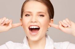 Mujer con los fingeres en oídos Fotografía de archivo libre de regalías