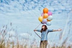 Mujer con los globos coloridos en el prado fotografía de archivo libre de regalías