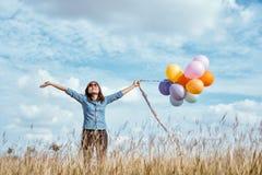 Mujer con los globos coloridos en el prado imagenes de archivo