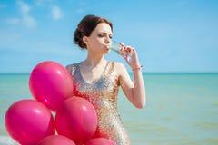 Mujer con los globos en el mar Imagen de archivo libre de regalías