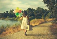 Mujer con los globos y la maleta coloridos en un campo imagen de archivo libre de regalías