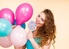 Mujer con los globos y la piruleta coloridos Imagen de archivo libre de regalías
