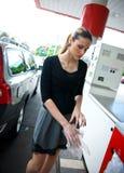 Mujer con los guantes protectores en la gasolinera Imágenes de archivo libres de regalías