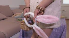 Mujer con los huevos de Pascua y los oídos del conejito