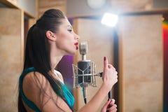 Mujer con los labios rojos que sostienen un micrófono y que cantan Imágenes de archivo libres de regalías