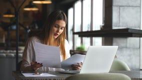 Mujer con los labios rojos que trabajan con su ordenador portátil y que comprueban el documento almacen de video