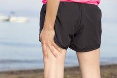 Mujer con los músculos heridos de la pierna durante entrenamiento imagen de archivo libre de regalías