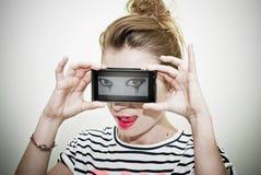 Mujer con los males de ojo en el teléfono elegante Imagen de archivo